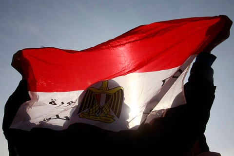 The shadow of an anti-Mubarak protester is seen as he holds an Egyptian flag in front of riot police in Cairo