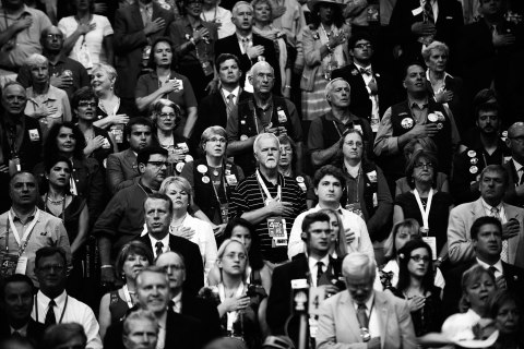 image: Delegates listen to the National Anthem on the final day of the Republican National Convention at the Tampa Bay Times Forum in Tampa, Florida, Aug. 30, 2012.