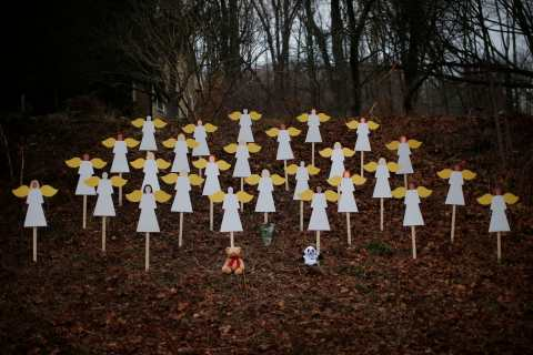 image: Twenty-seven wooden angel figures are seen placed in a wooded area beside a road near the Sandy Hook Elementary School for the victims of a school shooting in Newtown, Conn., Dec. 16, 2012.