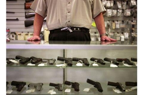 Image: Man resting hands on gun display case