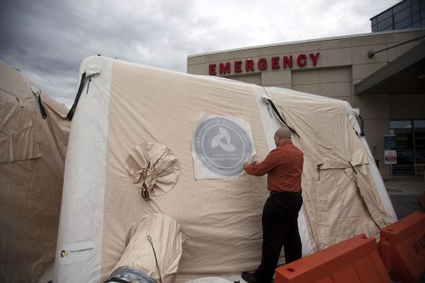 image: Luis Puentes, Director of Emergency Preparedness at Lehigh Valley Health Network's main hospital campus, applies a decal to a mobile tent set up to handle the recent influx of flu cases in Allentown, Pa., Jan. 11, 2013.