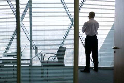 Business man looking out window of corner office