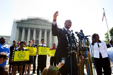 Ryan Haygood, the Director of the NAACP Legal Defense and Educational Fund, gathers with civil rights activists outside the Supreme Court to protest the high court's decision to strike down part of the Voting Rights Act of 1965 in Washington, D.C., on 25 June 2013.