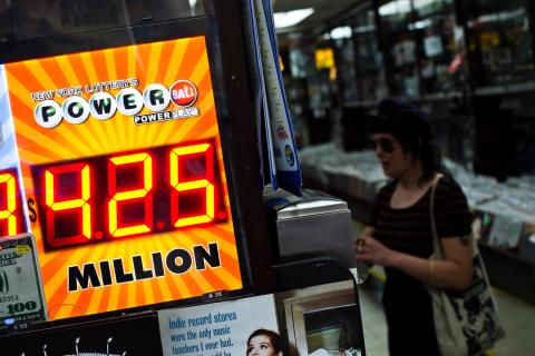 A woman buys a Powerball lottery ticket at a convenience store in New York City, on Aug. 7, 2013.
