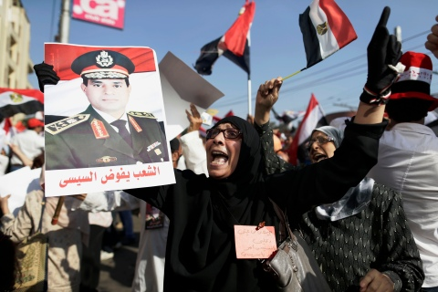An opponent of Egypt's ousted President Mohammed Morsi holds up a poster depicting General Abdel-Fattah el-Sissi, during a protest near the presidential palace in Cairo, on July 26, 2013.