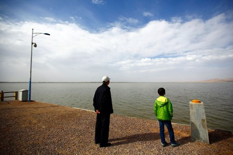 Visitors look at the Hongyashan water reservoir on the outskirts of Minqin town, Gansu province Sept. 20, 2013.