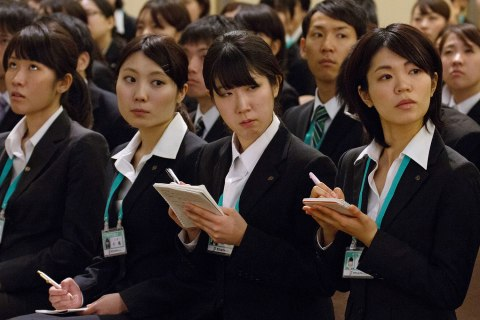 New employees take notes during a speech by Toshifumi Suzuki, chairman and chief executive officer of Seven & I, unseen, at an initiation ceremony in Tokyo, Japan, on Thursday, March 14, 2013.
