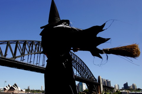 A girl wearing a witch costume stands in front of the Sydney Harbour Bridge and Opera House as ...