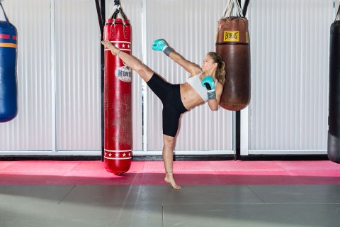 Ronda Rousey kicks leg up toward punching bag