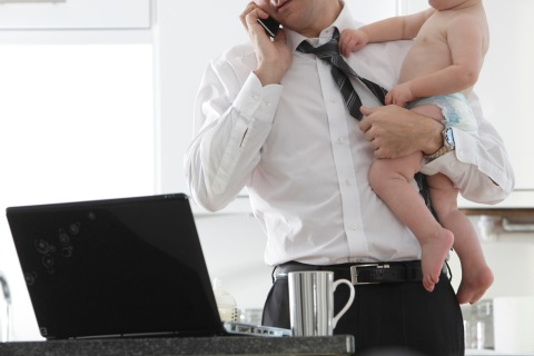 Father trying to work while holding baby