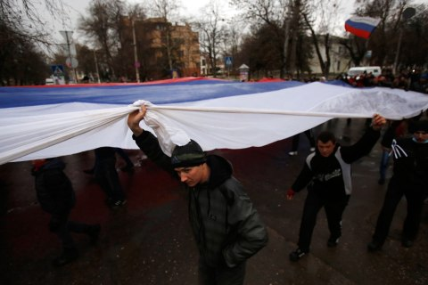 Pro-Russian demonstrators march with a huge Russian flag during a protest in front of a local government building in Simferopol, Crimea, Ukraine, Feb. 27, 2014.